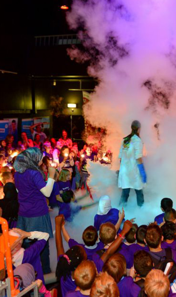 Mad scientist performing on stage surrounded by kids standing in a cloud of smoke